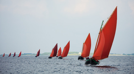 Traditional wooden boat Galway Hooker, with red sail, compete in regatta. Ireland.