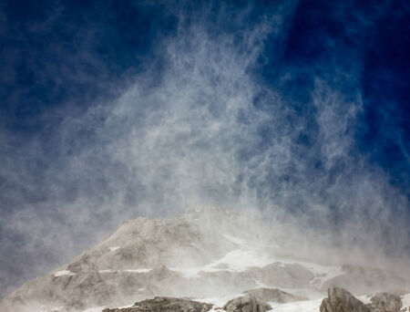 high winds: High winds close to the peak of the Jade Dragon Snow Mountain cause snow to rise into the air.