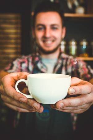 Happy barista offering cup of coffee Фото со стока
