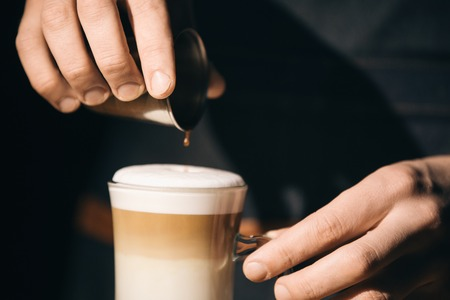 Hand on the barista, making a latte cafe, a cup of coffee with a beautiful latte Фото со стока