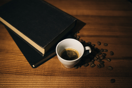 A cup of black coffee and coffee beans and a book on a wooden table. top view.