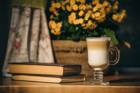 cup of latte or cappuccino coffee with a book