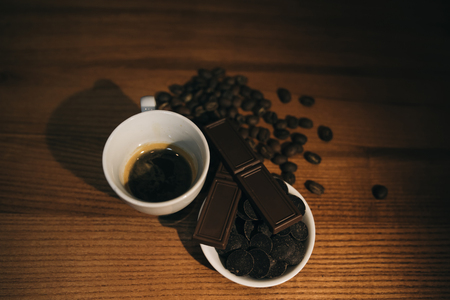 Cup of coffee with grains and chocolate on wooden table Фото со стока