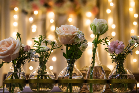 White and pink roses in vases, vintage home decor on the table, Фото со стока