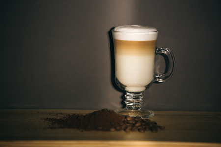 cup of latte or cappuccino coffee and brown coffee grounds