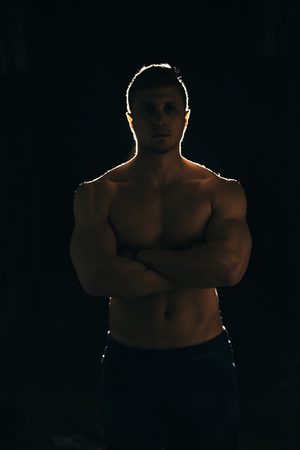 Silhouette of a strong man with dramatic light and dark background
