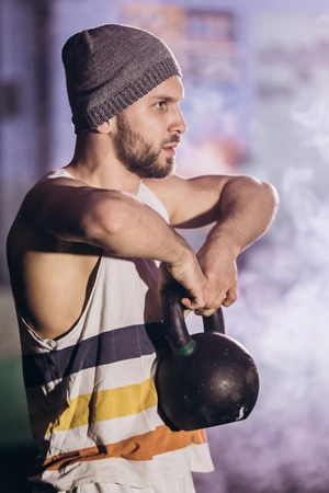 Handsome man doing exercise with dumbbells.