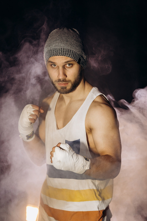 Young boxer fighting with bandaged fists Фото со стока