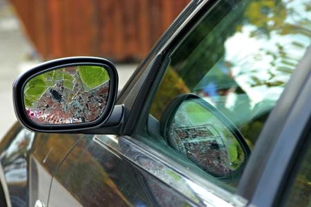 Broken left car mirror and blurry background