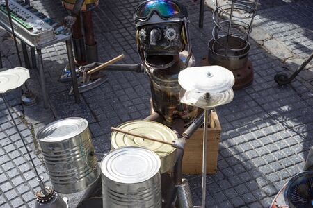 playing the market: A man made of tin playing the drums on the street