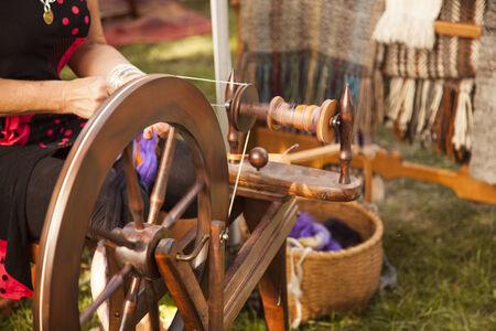 woman's clothing: woman at spinning wheel making yarn Stock Photo