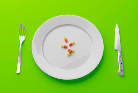 pills on an empty plate with knife and fork
