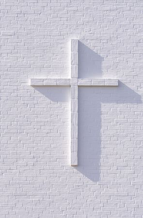 Cross on a white brickwall