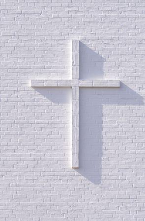 Cross on a white brickwall