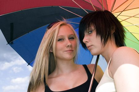 lesbianism: two girls with a rainbow colored parasol Stock Photo