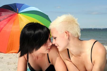 parasol: Two girls flirting on the beach Stock Photo