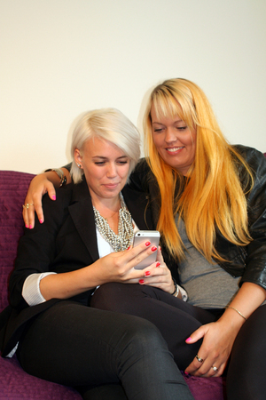 two young women reading text message photo