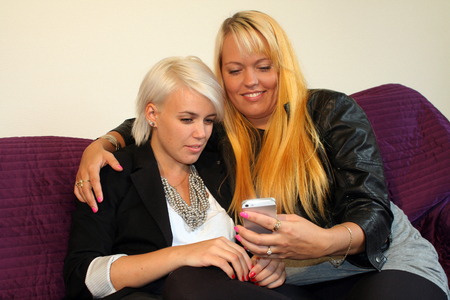 lesbianism: two young women reading text message Stock Photo