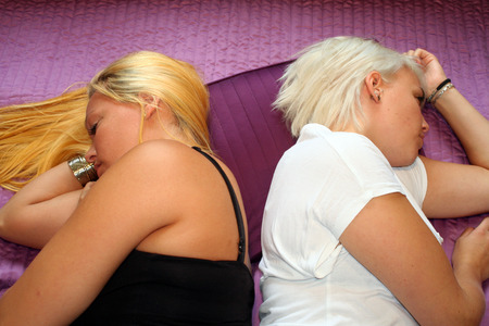lesbianism: two young women lying in bed back to back