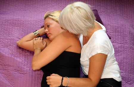 lesbianism: two young women lying in bed Stock Photo