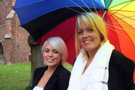 lesbianism: two young women holding a rainbow colored umbrella Stock Photo