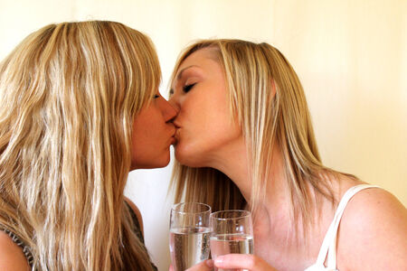 lesbian woman drinking champagne and kissing photo