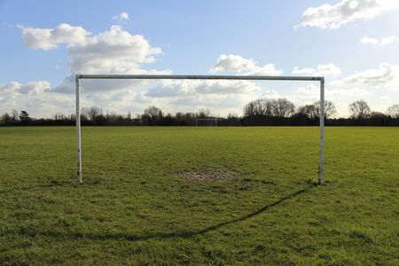 motivations: Goal Posts On A Field In The Sun With Blue Sky And Clouds