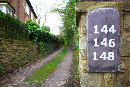 overgrown: Long Overgrown Pathway With Slate Numbers On A Wall Stock Photo