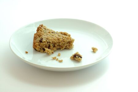 Flapjack oat bar on a white plate isolated on white photo