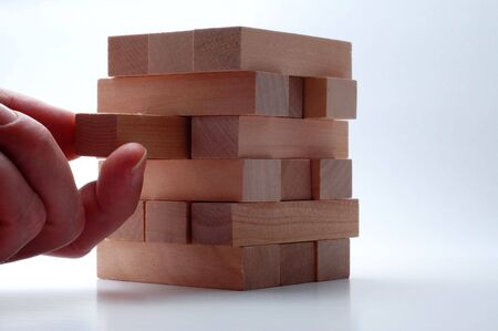 stacking: Fingers removing a wooden block from the tower Stock Photo