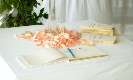 guests: Wedding guest book and order of service sheets on table with rose petals