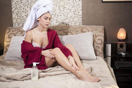 beine spreizen: Schöne Mädchen im Schlafzimmer, die Sahne auf die Beine nach der Dusche