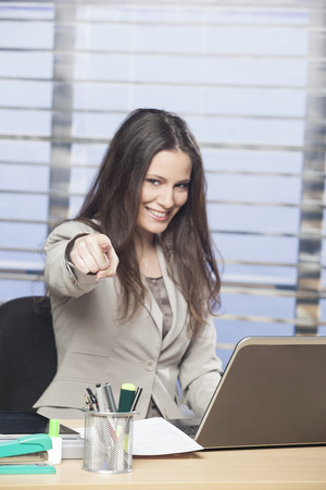 Businesswoman pointing finger at camera photo