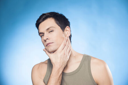 shaved: Man touching his face after shaving Stock Photo