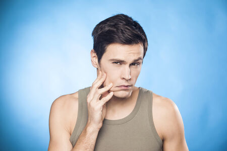 aging face: Man touching his face and frowning, worried about aging Stock Photo