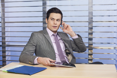 Successful businessman talking on the phone and holding tablet photo