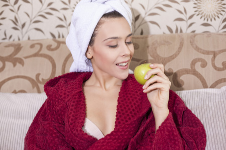 red bathrobe: Woman in bathrobe eating apple