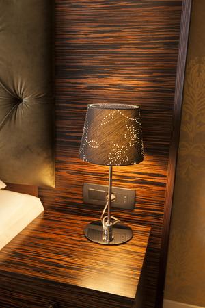 bedside: Bedside lamp on a wooden bedside table