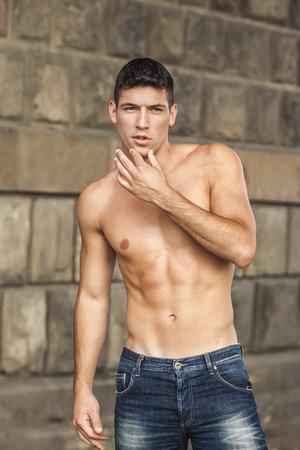 Muscular shirtless man outdoors
