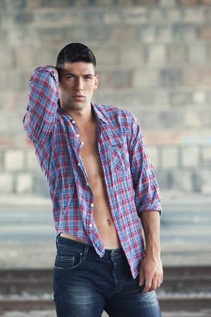 lumberjack shirt: Man posing in unbuttoned plaid shirt Stock Photo