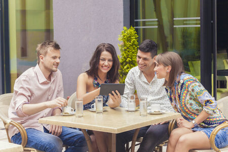 Friends looking at pictures on tablet in cafe photo