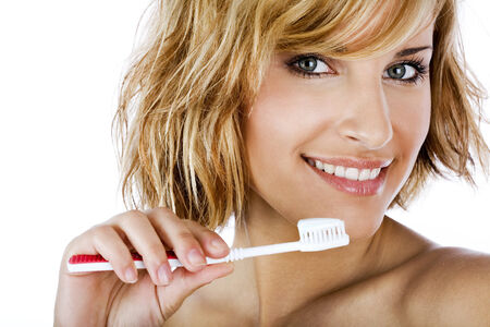 tooth paste: Beautiful woman brushing teeth isolated on white