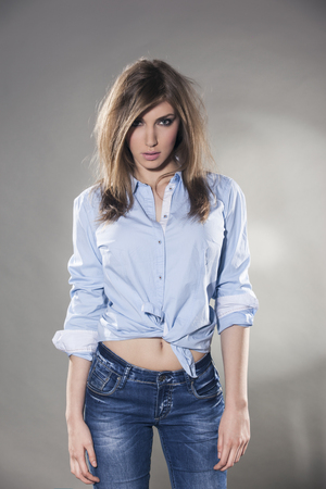 tied in: Young woman in jeans and tied shirt
