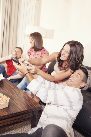 Couple hanging out with friends and fighting over remote control photo