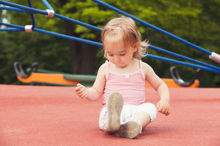 sitting on the ground: Cute little girl sitting on the ground Stock Photo