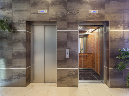 Two elevators shot from outside, one open and other closed photo