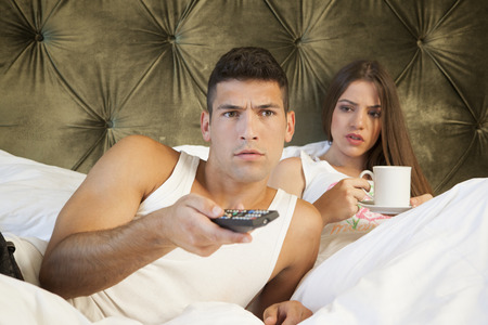 Man watching TV while his girlfriend is looking annoyed photo