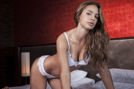 girl boobs: Sexy woman in white lingerie posing on bed Stock Photo