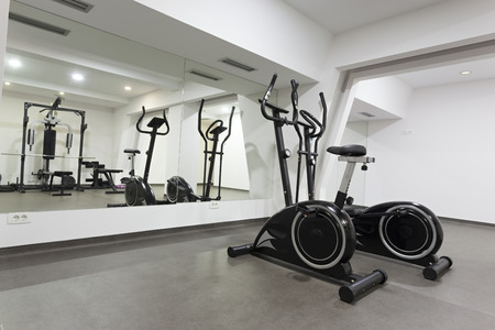 Elliptical trainer and bike in exercise room photo