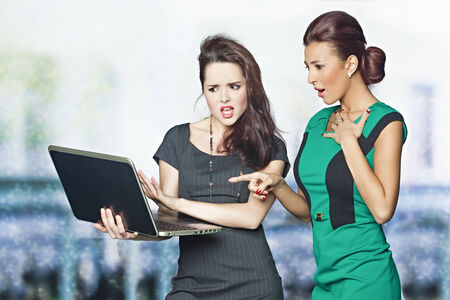 appalled: Two businesswomen looking at computer screen shocked